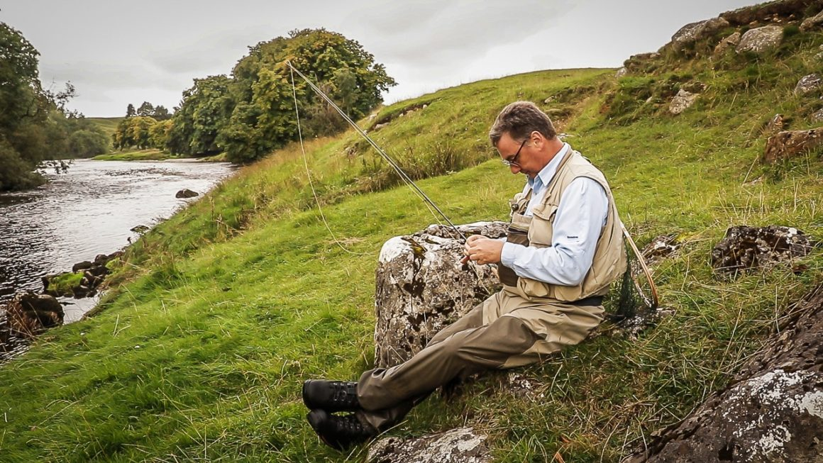 flyfisherman sat beside river wharfe